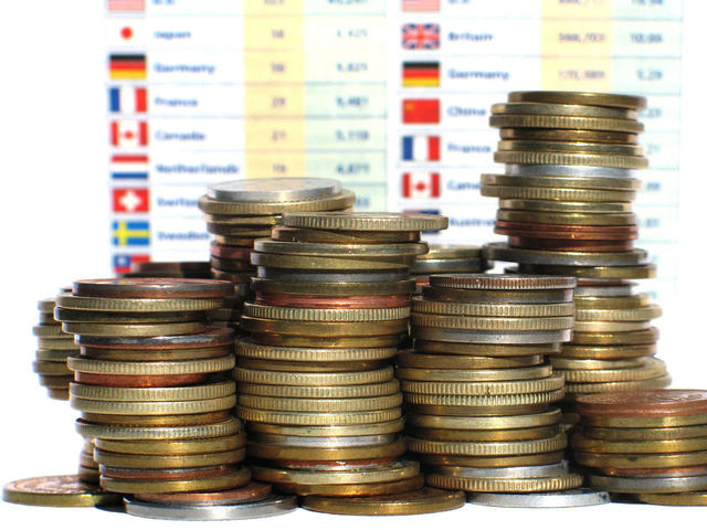 kopa mincí stojící před kurzy měn